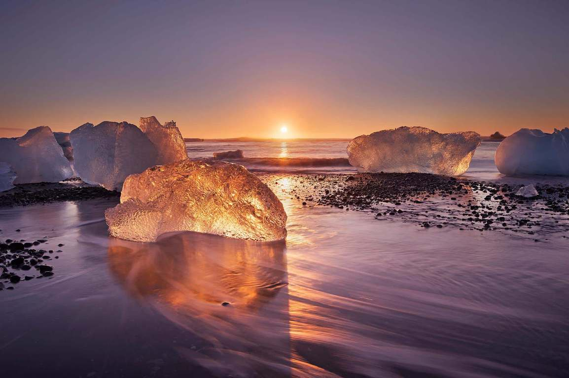 Pieces of ice glistening in the sun at sunrise on Diamond beach in Iceland